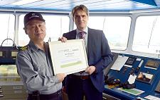 Auf der Brücke: Kapitän Gyeong Sig Lee nimmt die Auszeichnung von bremenports-Geschäftsführer Robert Howe entgegen.