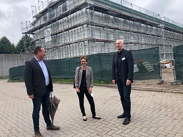 Marko Rothaar (links), zuständig für Liegenschaften im Justizressort und der Leiter der JVA, Hans-Jürgen Erdtmann (rechts) erläuterten Senatorin Claudia Schilling den Baufortschritt des neuen Container-Hafthauses im Hintergrund. Foto: Justizressort